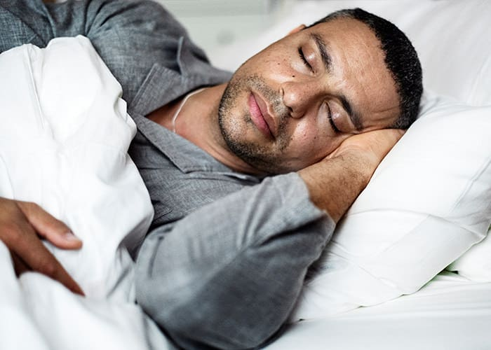 Man laying in bed during deep sleep after float therapy session in London
