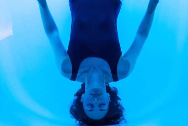Woman floating on back in water of floatation tank in London