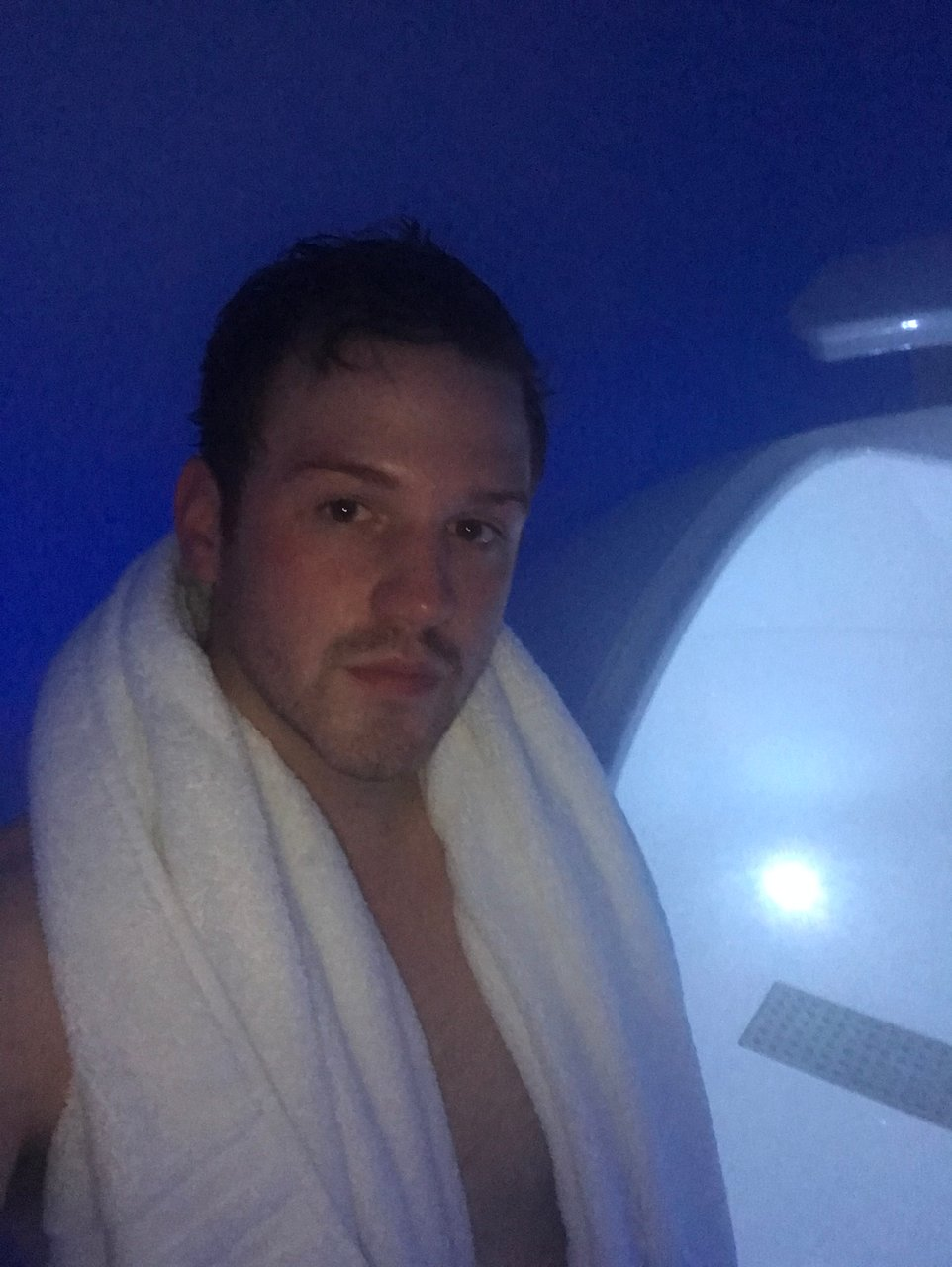Man with towel around neck standing outside floatation tank in London spa